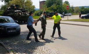 A man bends and puts trousers off at US military parade in Czechia. Video
